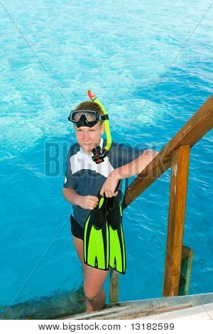 Boy-teenager with flippers mask and tube at ocean. Maldives.