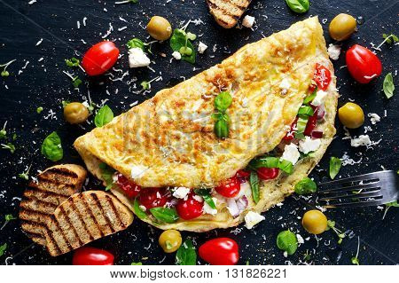 Vegetables Omelette with tomatoes, basil, greek cheese, parmesan, olives, grilled toast. on stone board.
