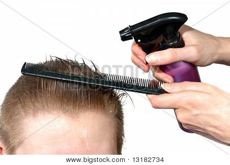 The hairdresser moistens hair to the client before a hairstyle
