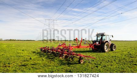 Farmer at work with a hay tedder attached to the tractor. On the field there is a long row of high voltage pylons with cables for electricity distribution.