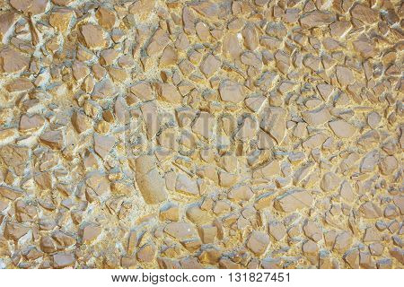 Concrete panel surface is covered with gravel and painted in brown