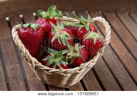 Side View Of Strawberries In Small Basket Under Wooden Background