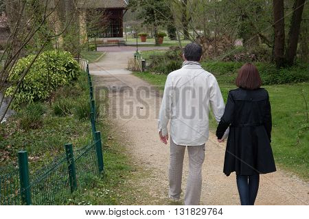Couple Walking In The Spring Garden, Holding Their Hands.