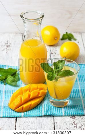 mango ice tea with mint in a glass and bottle on a napkin blue and white wooden background