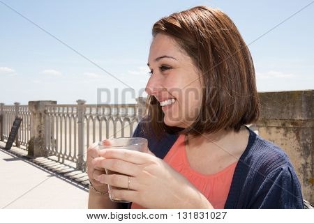 Woman Sitting On Beach With Cup Of Hot Beverage