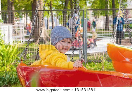 cheerful little boy having fun at the amusement park