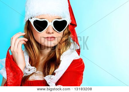 Beautiful young woman in Santa Claus clothes over pink background.