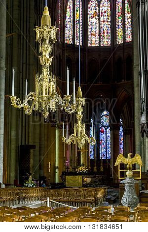 REIMS, FRANCE - MAY 15, 2013: There are details of decoration Reims Cathedral - massive gilded chandeliers.