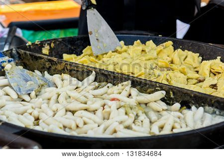 Chef serving tasty mix of gnocchi and pasta. Street food photography.