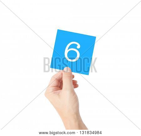 6 written on a card held by a hand