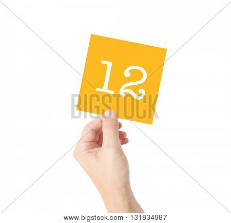 12 written on a card held by a hand