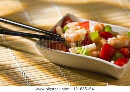Shrimp salad inside a white bowl and chopsticks over a bamboo tablecloth