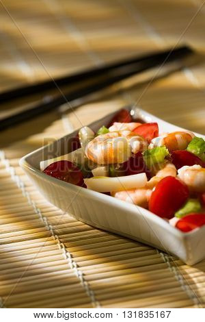 Shrimp salad with squid tomatoes celery inside a white bowl on a bamboo tablecloth and chopsticks