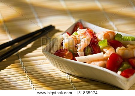 Close up of shrimp salad with squid tomatoes celery inside a white bowl over a bamboo tablecloth and chopsticks