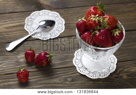 ripe strawberries in a cup of ice cream and berries on a wooden table a teaspoon on a napkin