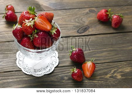 ripe strawberries in a cup of ice cream on a white napkin and berries on a wooden table