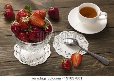 red ripe strawberries in a glass of ice cream and a cup of tea with a spoon