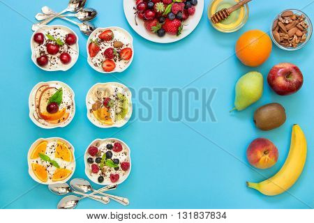 Left 6 yogurts displayed vertically in 2 rows near empty space and around plate of berries fruits nuts honey 6 spoons on light blue background. Six yogurts ingredients and empty space. Top view.