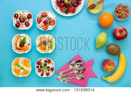 6 yogurts displayed vertically in 2 rows near empty space and around plate of berries fruits nuts honey 6 spoons napkins on blue background. Six yogurts ingredients and empty space. Top view.