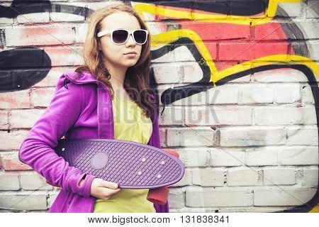 Blond Teenage Girl Holds Skateboard, Portrait
