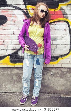 Blond Teenage Girl Holds Skateboard, Vertical Photo