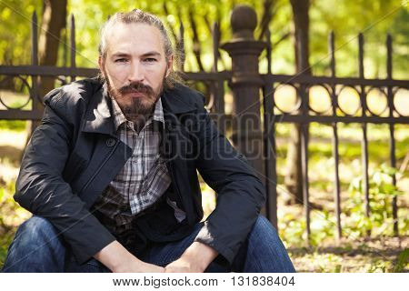 Young Bearded Asian Man Sitting In Summer Park