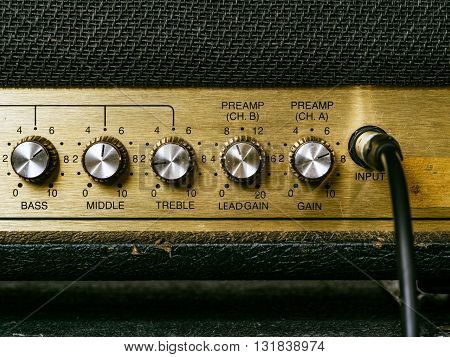 Macro photo of a vintage electric guitar amplifier showing the knobs and input plug.