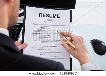 Cropped image of businessman analyzing resume at desk in office