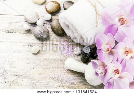 Spa setting with pink orchid herbal massage ball and essential oil. Wellness concept