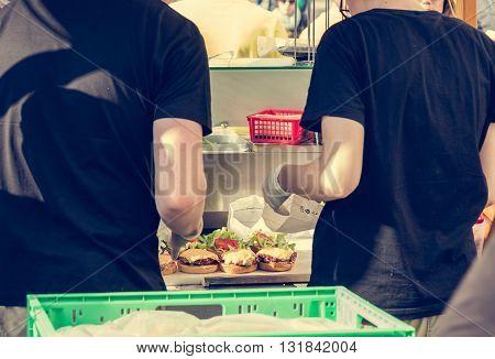 Chef preparing tasty burgers at outdoor stand. Teamwork sandwich making procedure.