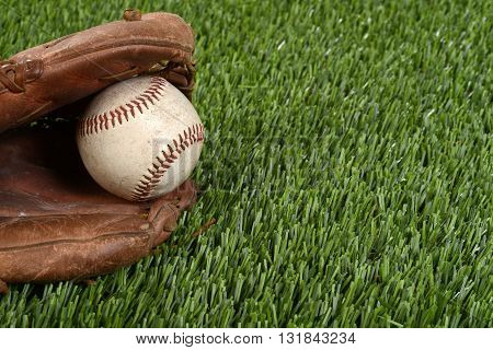 closeup baseball glove and ball on artificial grass