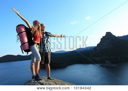 Couple of tourists are standing at the top of a mountain with a feeling of freedom.