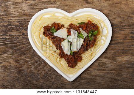 heart shaped pasta dish on dark wood