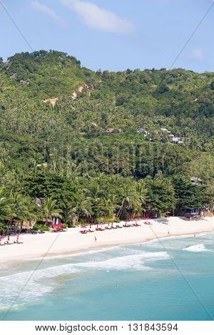 KOH PHANGAN THAILAND - NOVEMBER 21 2015 : Beautiful Thong Nai Pan Noi Beach with palm trees and bungalows for tourists. On the island Koh Phangan each month passes full moon party for tourists