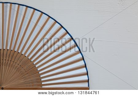 Typical Japanese hand fan made on the wooden white table