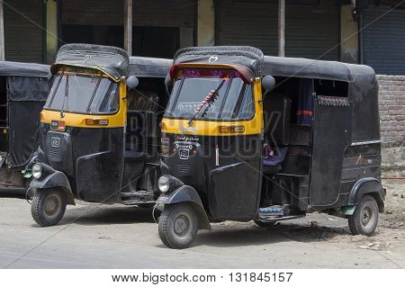 SRINAGAR INDIA - JULE 02 2015: Auto rickshaw taxis on a road in Kashmir India. These iconic taxis have recently been fitted with CNG powered engines in an effort to reduce pollution