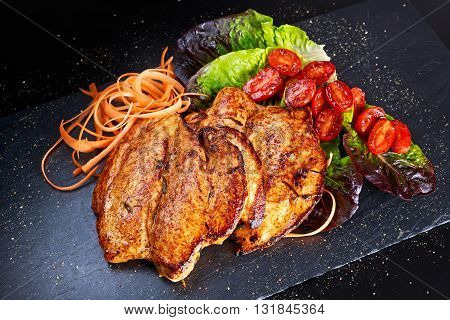 Grilled chicken breast steaks with grilled cherry tomatoes, curly carrots on salad leaves on stone board.