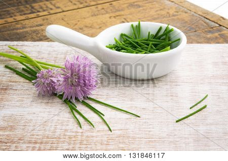 chopped chives with flowers window lit for soft focus on wood grain