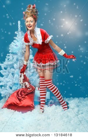 Fashionable young woman in Santa Claus clothes with presents over black background.