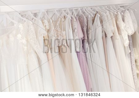 Beautiful wedding dresses with various designs hanging on the stand