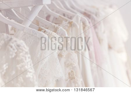 Close up of white wedding dresses hanging on rack