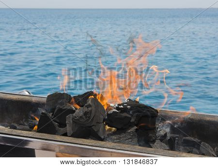 Charcoal BBQ barbecue coals burning on fire with tropical ocean background