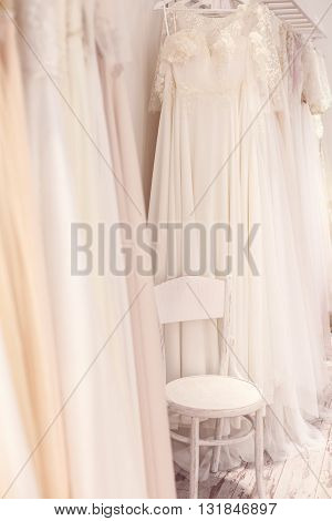 Wide assortment of elegant wedding dresses hanging on rack. There is a chair between them in boutique