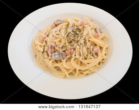 Pasta Carbonara with bacon on a white plate isolated on the black background with clipping path