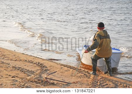 The man pulls the boat to the sandy Bank of the river