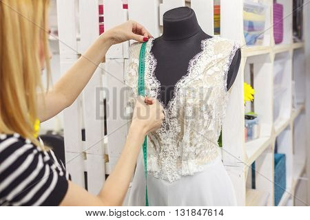 Skillful young designer is making a wedding dress. She is standing near a mannequin. The woman is measuring clothing with tape-line seriously