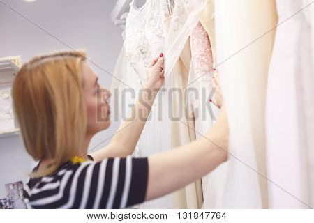 Talented fashion designer is working in atelier. She is touching cloth of wedding dress. The woman is standing and looking at clothing pensively