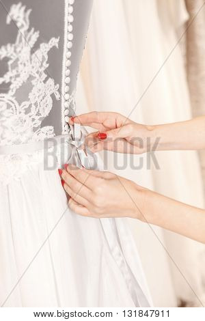 Close up of arms of designer tying bow on wedding dress