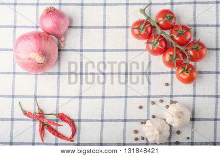 Frame Of Pepper, Garlic, Onion, Tomatoes On Squared Cloth Table