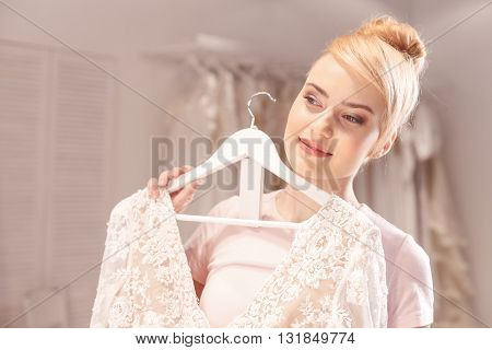 Portrait of pretty young woman dreaming about her wedding. She is standing and holding dress near her body. She is smiling with happiness